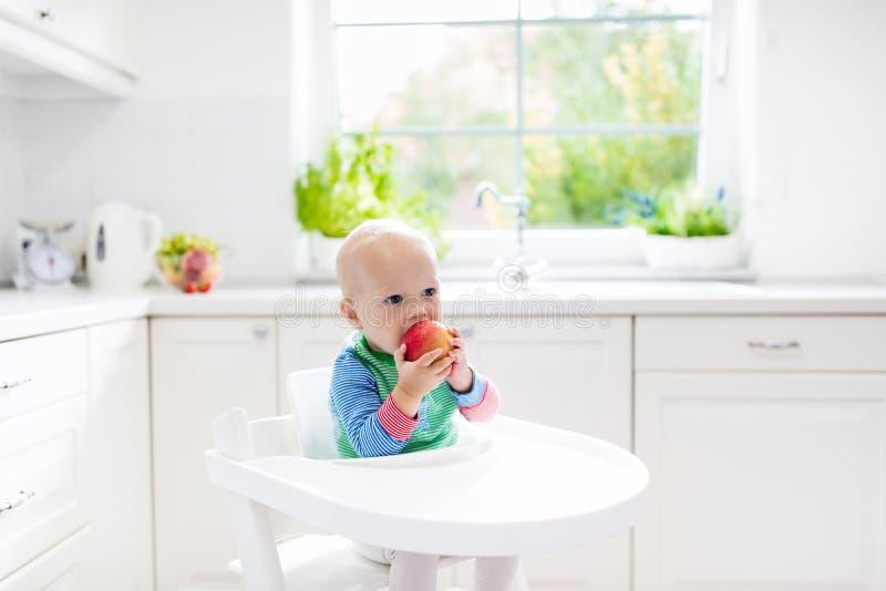 Bebê que come a maçã na cozinha branca em casa fotografia de stock royalty free