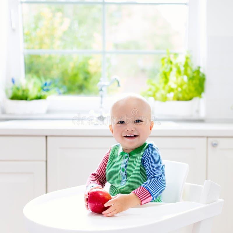 Bebê que come a maçã na cozinha branca em casa imagem de stock