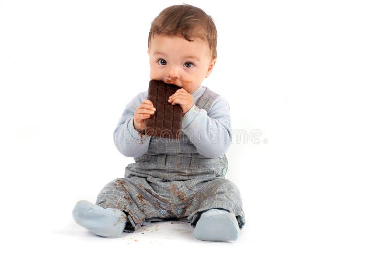 Bebê que come o chocolate imagem de stock