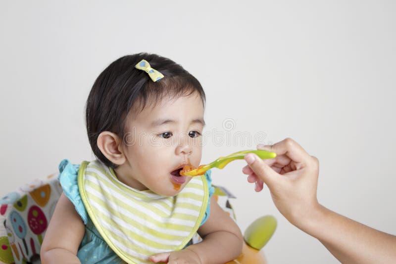 Bebê que come o comida para bebê imagem de stock