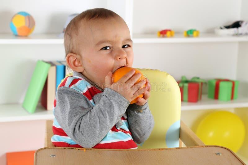 Bebê que come o fruto alaranjado fotografia de stock royalty free