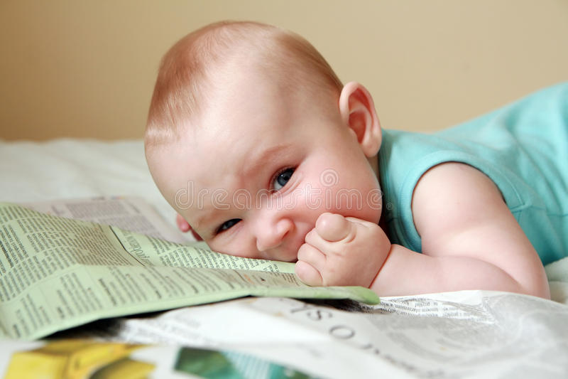 Bebê que come o jornal imagens de stock royalty free