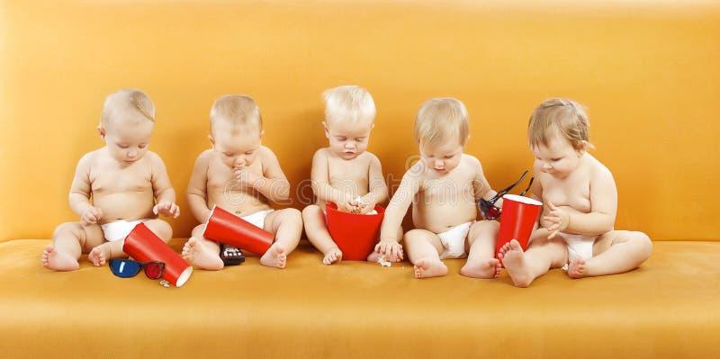 Bebê que come a pipoca, grupo das crianças que olha a tevê, crianças um ano imagens de stock royalty free
