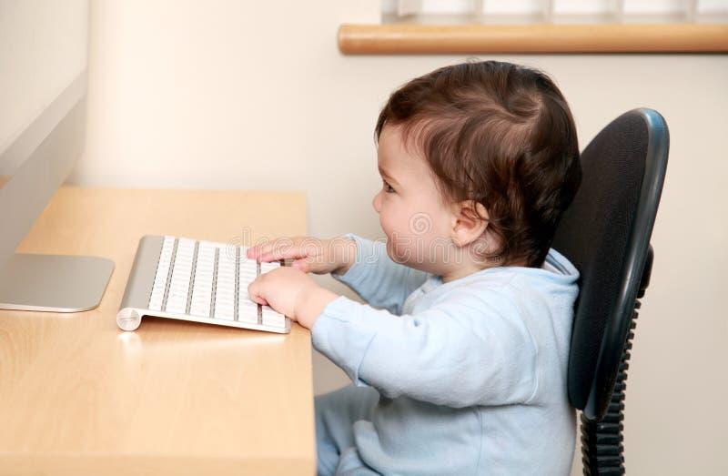 Bebê que datilografa no computador fotografia de stock