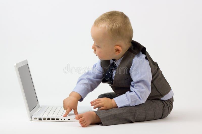 Bebê que datilografa no portátil imagem de stock