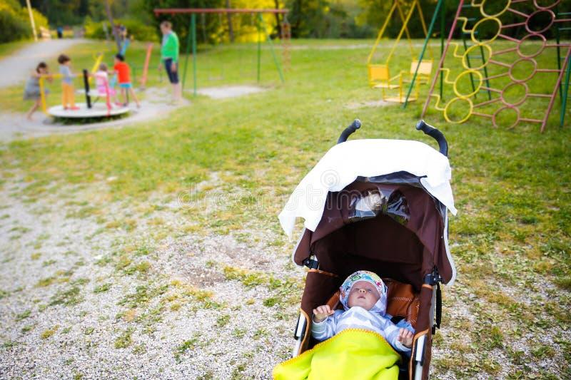Bebê que descansa em um carrinho de criança no campo de jogos imagens de stock
