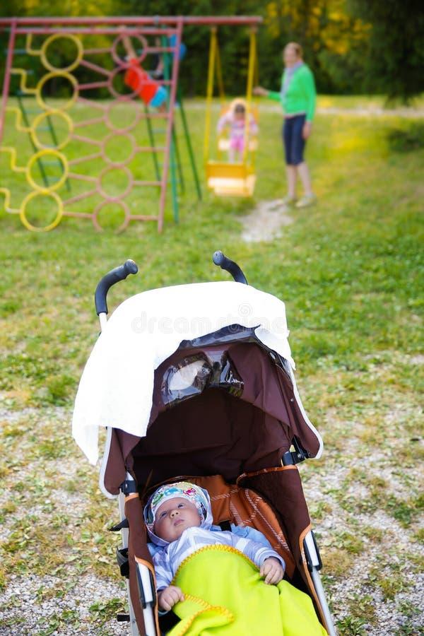 Bebê que descansa em um carrinho de criança no campo de jogos imagem de stock royalty free