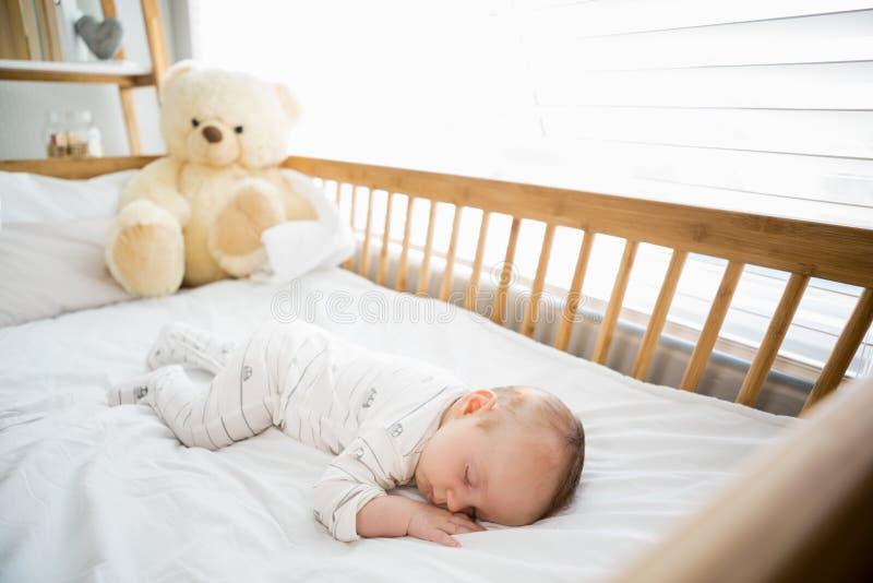 Bebê que dorme em um berço imagem de stock
