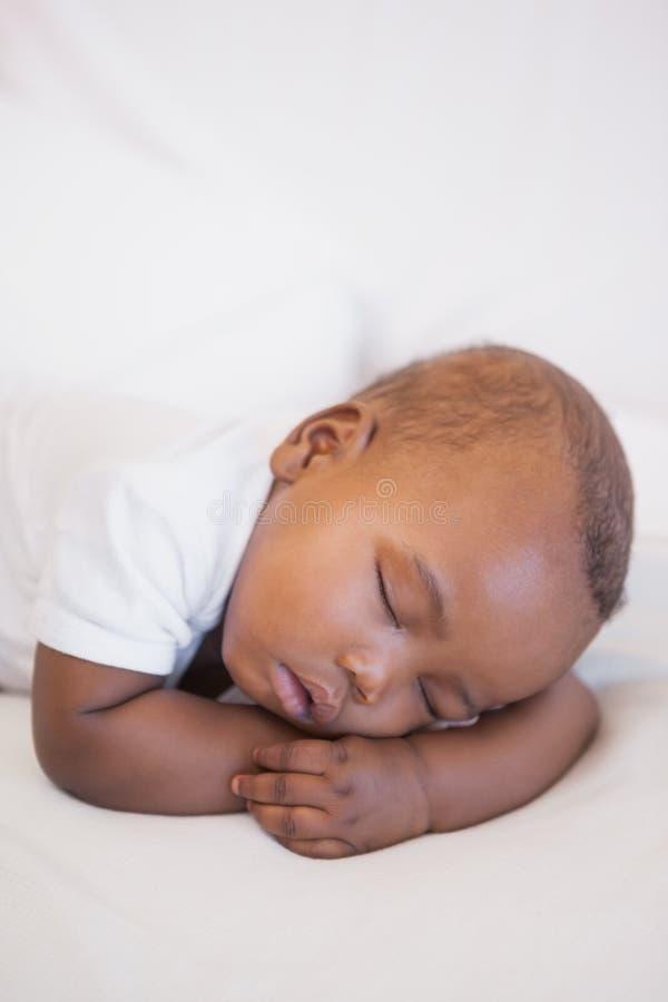 Bebê que dorme pacificamente no sofá imagens de stock