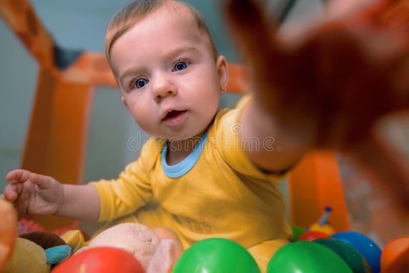 Bebê que encontra-se entre as bolas coloridas que alcançam para fora para brinquedos imagens de stock royalty free