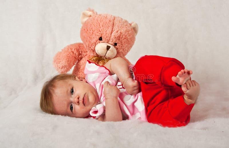 Bebê que encontra-se girly na frente de um teddie cor-de-rosa fotografia de stock royalty free
