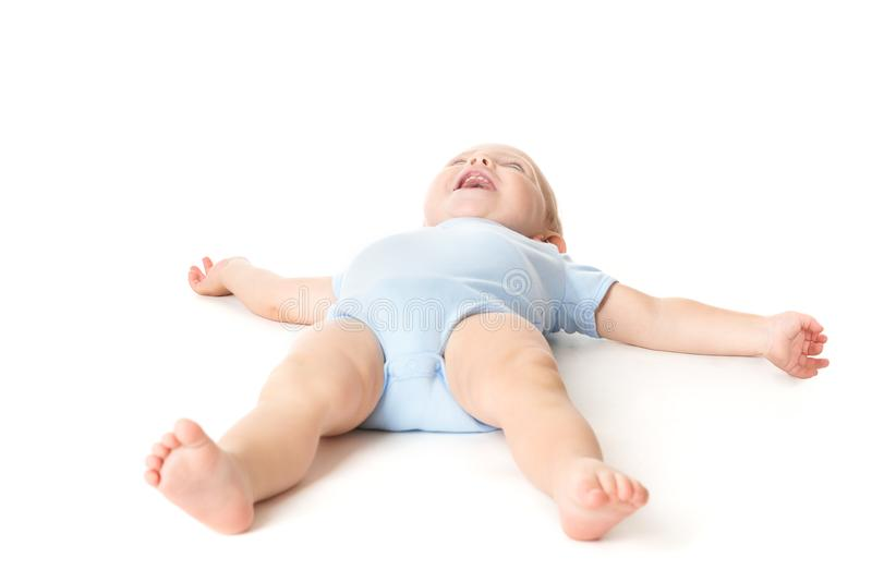 Beb? que encontra-se na crian?a infantil branca, feliz na crian?a traseira, engra?ada do menino fotos de stock royalty free