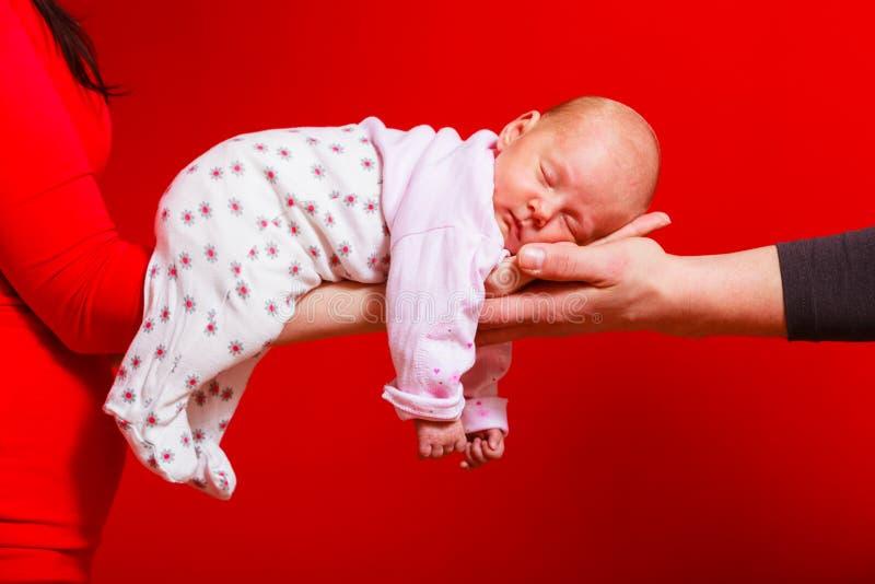 Bebê que encontra-se nos braços da mãe e do pai fotos de stock royalty free