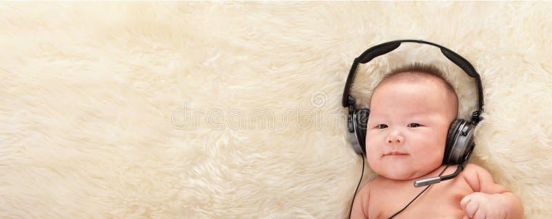 Bebê que escuta a música fotos de stock