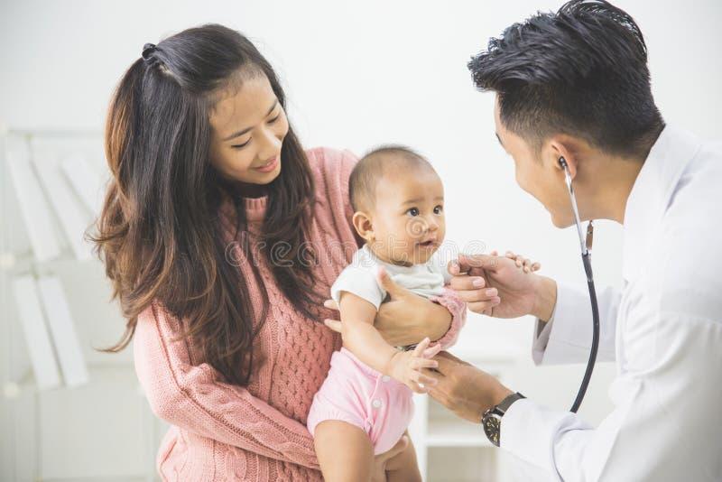 Bebê que está sendo verificado por um doutor imagem de stock