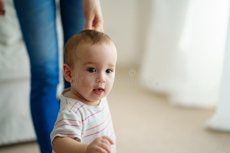 Bebê que executa primeiramente etapas com apoio da mãe fotos de stock