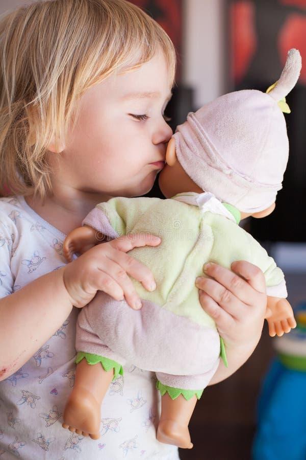 Bebê que fala à boneca da orelha fotos de stock