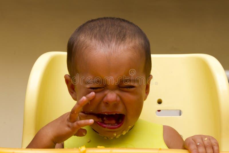 Bebê que grita ao comer imagem de stock