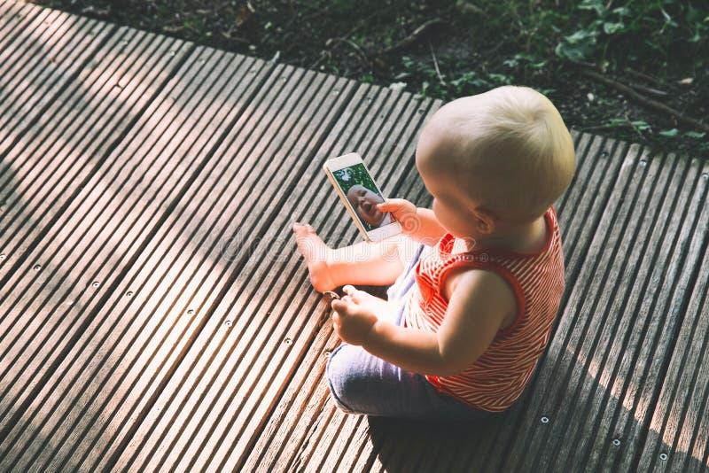 Bebê que guarda o smartphone e que toma o selfie engraçado com câmera imagem de stock royalty free