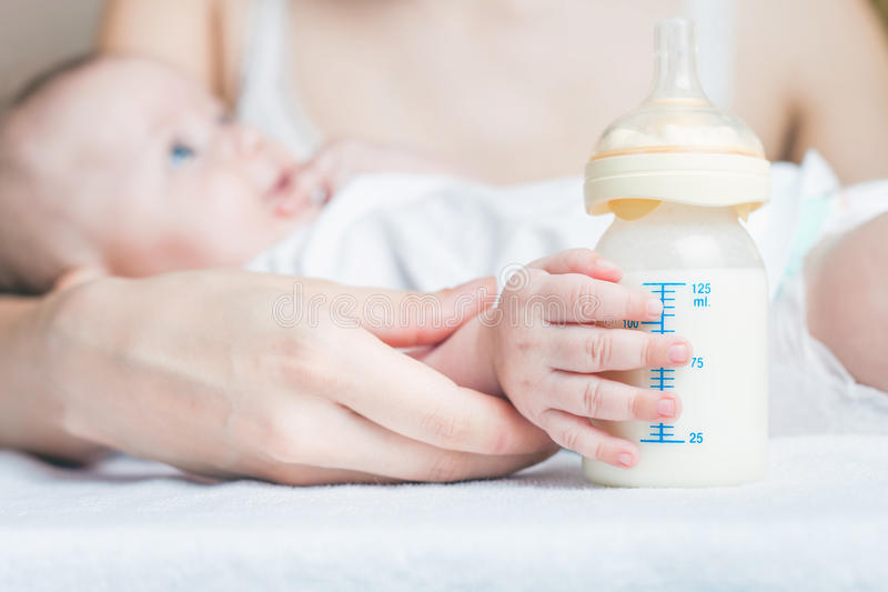 Bebê que guarda uma garrafa de bebê com leite materno imagens de stock royalty free