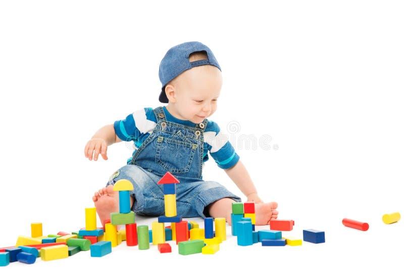 Bebê que joga blocos dos brinquedos, tijolos de construção coloridos do jogo da criança, criança de um ano no branco foto de stock royalty free