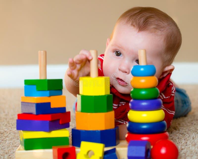 Bebê que joga com empilhamento do brinquedo de aprendizagem imagens de stock