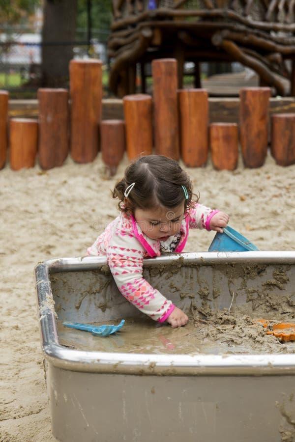 Bebê que joga com lama foto de stock