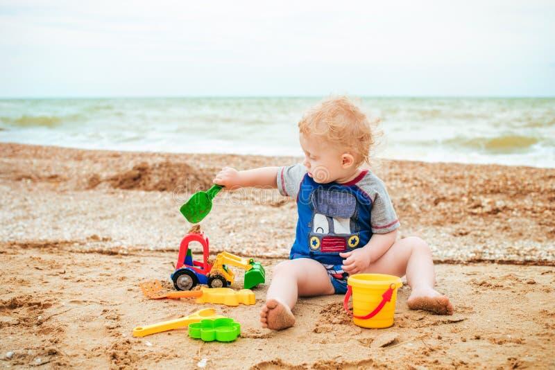 Bebê que joga com o brinquedo no mar foto de stock royalty free