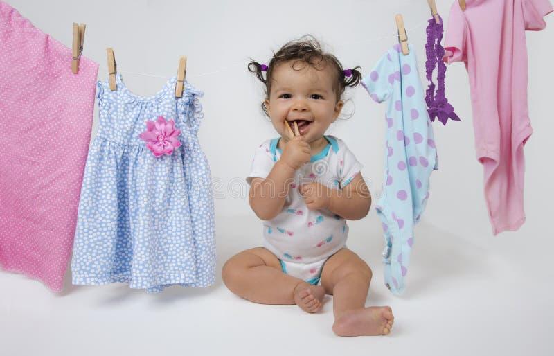 Bebê que joga com o pregador de roupa na linha da lavanderia imagens de stock royalty free