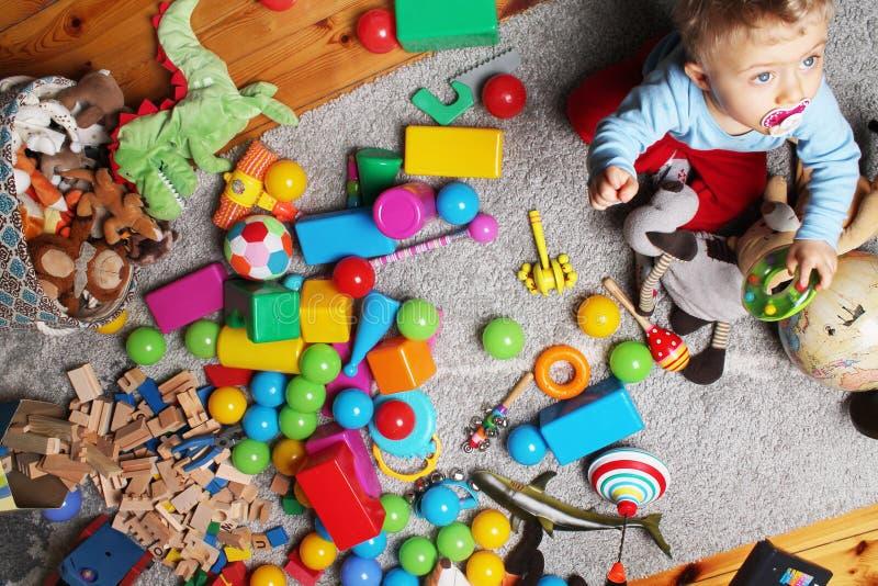 bebê que joga com seus brinquedos no assoalho fotografia de stock royalty free