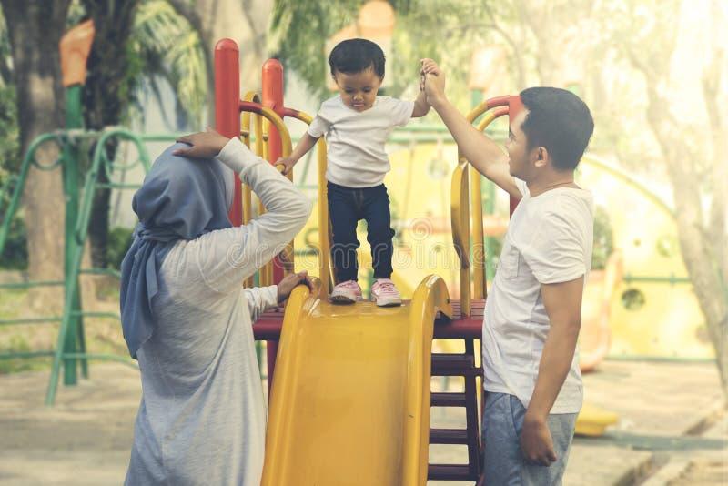 Bebê que joga com seus pais no parque foto de stock royalty free