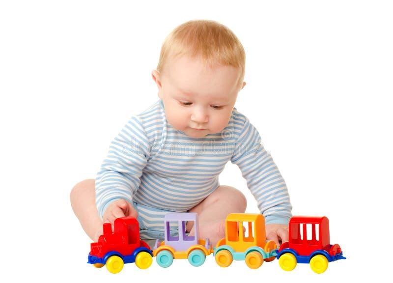 Bebê que joga com trem do brinquedo fotos de stock royalty free