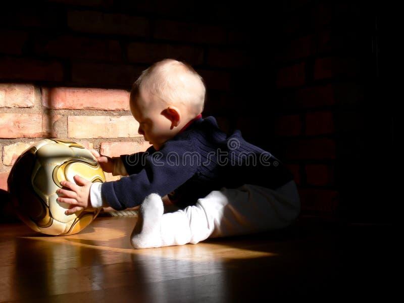 Bebê que joga com um futebol foto de stock royalty free