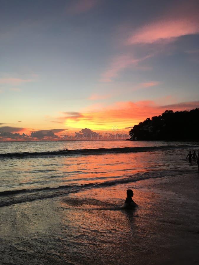 Bebê que joga em um oceano por do sol-iluminado! imagem de stock royalty free