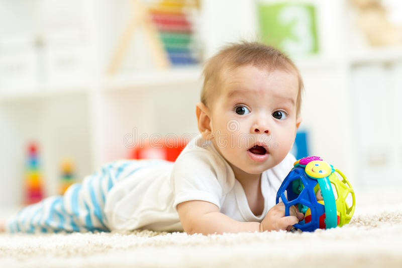 Bebê que joga em um tapete em casa foto de stock royalty free