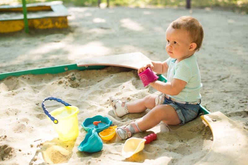 Bebê que joga na caixa de areia no campo de jogos exterior Crian?a com os brinquedos coloridos da areia O beb? ativo saud?vel for imagem de stock royalty free