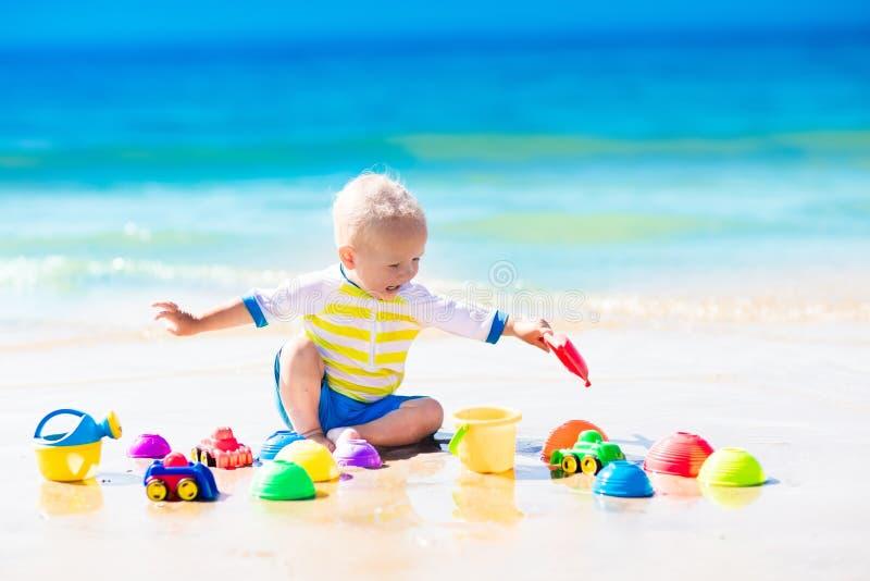 Bebê que joga na praia tropical que escava na areia imagem de stock