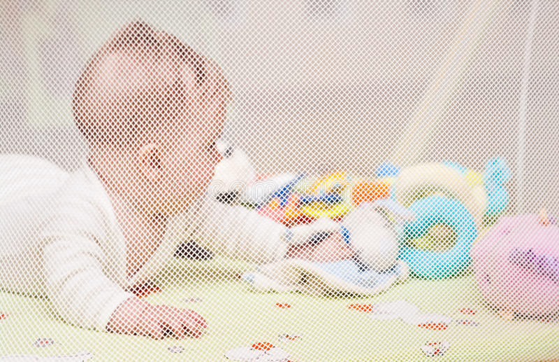 Bebê que joga no playpen fotos de stock royalty free