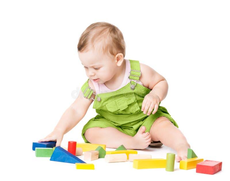 Bebê que joga os blocos dos brinquedos, jogo com os tijolos de construção coloridos, criança de um ano da criança no branco imagens de stock royalty free