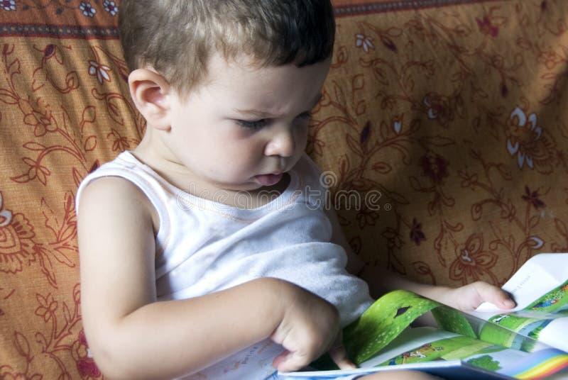 Bebê que lê o livro foto de stock