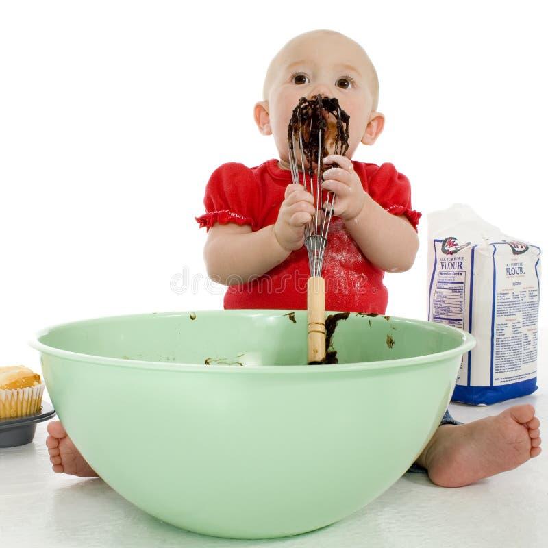 Bebê que lambe o misturador do bolo imagens de stock