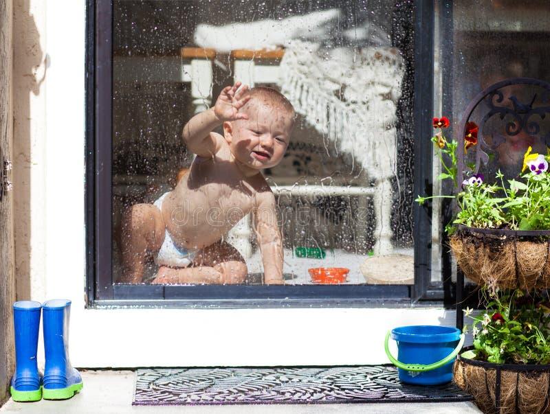 Bebê que olha através da janela no jardim em um dia chuvoso foto de stock