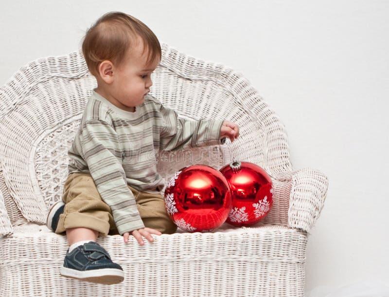Bebê que olha ornamento grandes do Natal foto de stock