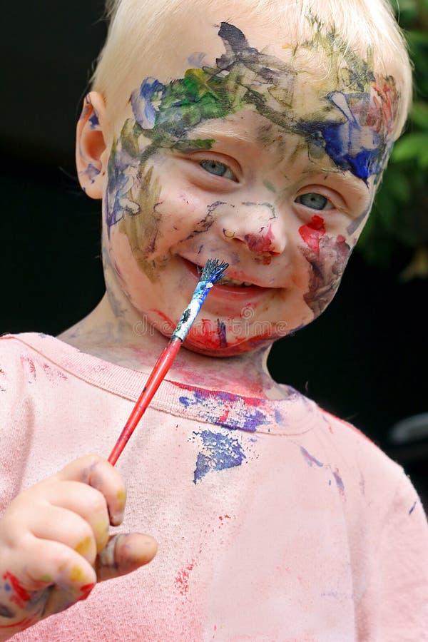 Bebê que pinta sua cara fotografia de stock