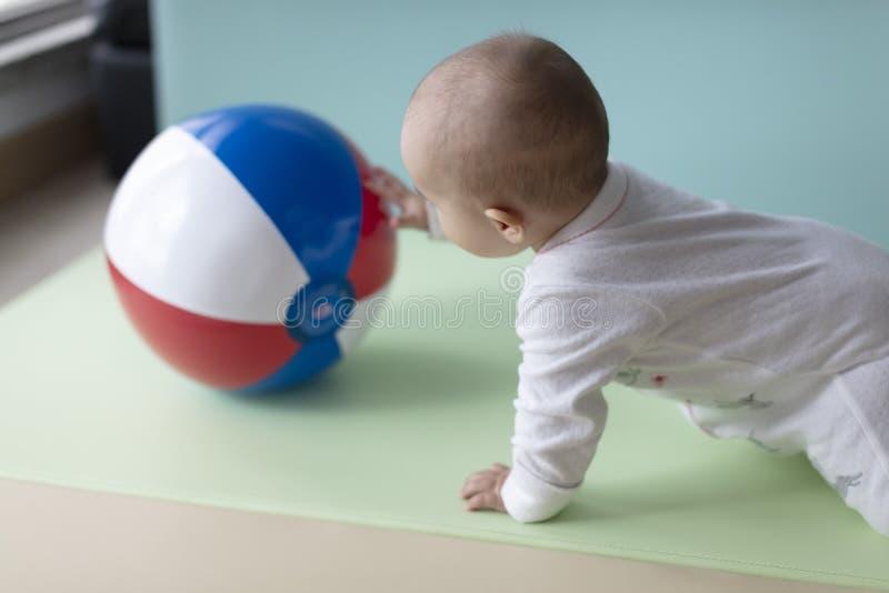 Bebê que rasteja para buscar uma grande bola colorida foto de stock royalty free