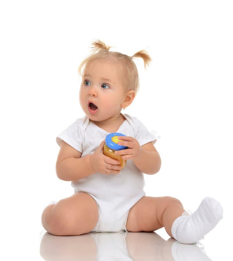 Bebê que senta e que guarda o frasco do alimento do puré da erva-benta da criança fotografia de stock