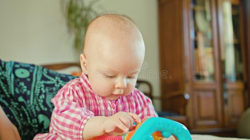 Bebê que senta-se e que joga com um brinquedo foto de stock royalty free