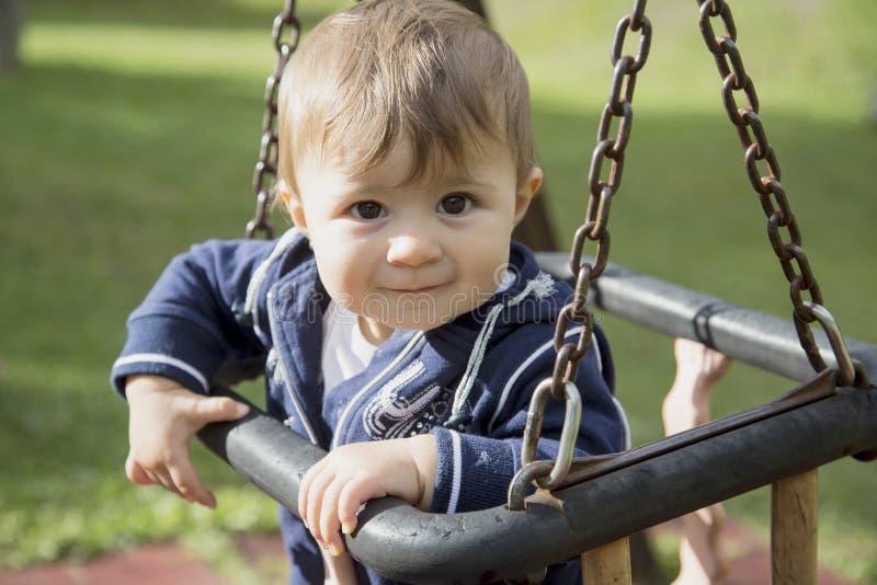 Bebê que senta-se em balanços fotografia de stock