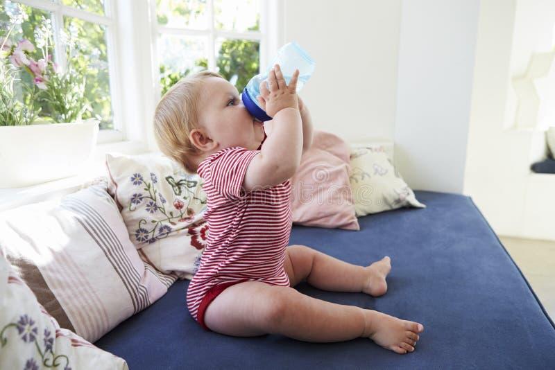 Bebê que senta-se em Seat pela janela que bebe do copo de formação imagem de stock