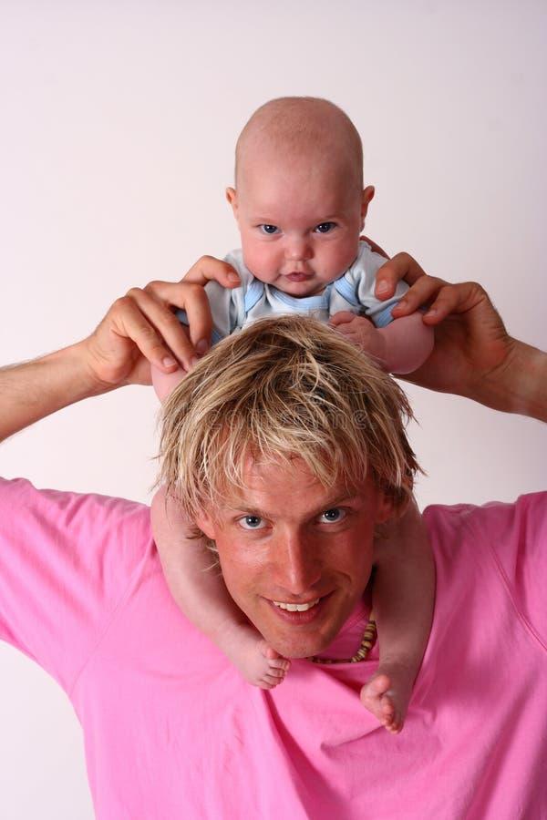 Bebê que senta-se em seu ombro dos pais imagens de stock royalty free